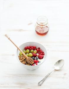 Healthy breakfast  Bowl of oat granola with yogurt  fresh berries  fruit and honey  Top view