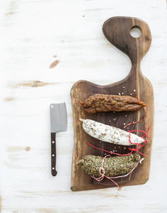 French alsacian smoked salamis on rustic walnut wooden chopping board over white backdrop  top view