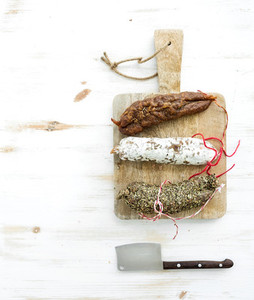 French alsacian smoked salamis on rustic wooden chopping board over white backdrop top view