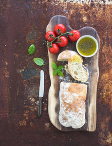 Freshly baked ciabatta bread with cherry tomatoes  olive oil  basil and salt on walnut wood board over grunge rusty metal background  top view