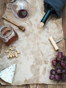 Wine and appetizer set with copy space in center Glass of red wine bottle corkscrewer blue cheese grapes honey walnuts on oily craft paper over rustic wooden table top view