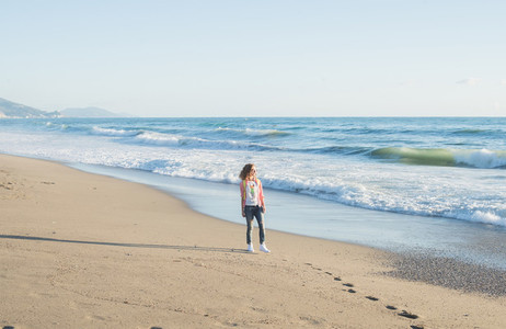 Young woman in red checkered shirt jeans white sneakers walking along beach and the stormy ocean on sunny winter day