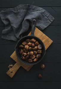 Roasted chestnuts in iron skillet pan on rustic wooden board over black table background top view