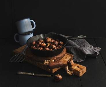 Roasted chestnuts in skillet cooking pan over rusti wooden boards  blue enamel mugs  towel on dark background