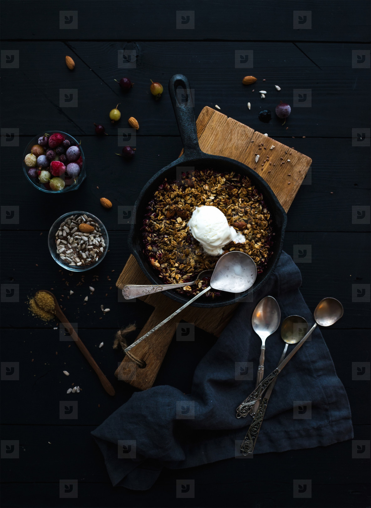 Healthy breakfast  Oat granola crumble with frozen fresh berries   seeds and ice cream scoopin irom skillet pan on rustic wooden board over dark backdrop