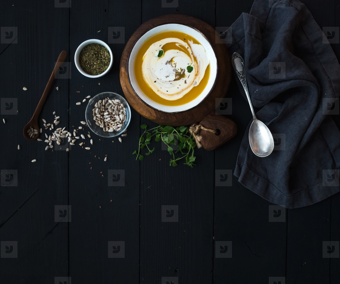 Pumpkin soup with cream  seeds and spices in rustic metal bowl over black background  Top view