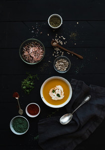Pumpkin soup with cream  seedsand various spicesl in rustic metal bowl over grunge black background  Top view