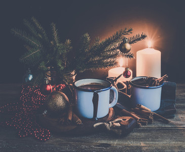 Christmas food and decorations set  Fur tree branches  mug of hot chocolate  colorful glass balls  burning candles  cinnamon sticks  dark background