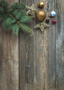 Christmas or New Year rustic wooden background with toy decorations  candy cane and fur tree branch  top view