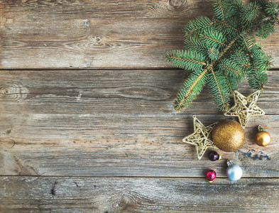 Christmas or New Year rustic wooden background with toy decorations and fur tree branch top view