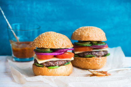 Fresh beef burger with cheese vegetables and spicy tomato sauce on paper blue wooden background