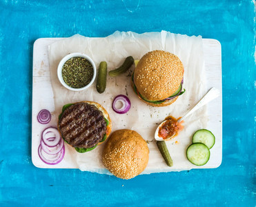 Fresh beef burger with cheese  vegetables  spicy tomato sauce on paper and white serving board  blue wooden background