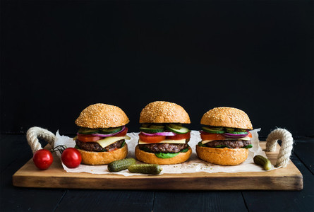 Fresh beef burgers with cheese  vegetables  pickles and spicy tomato sauce on paper over rustic wooden tray  black background
