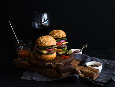 Fresh beef burgers on rustic wooden boards with glass of wine and tomato sauce  black background