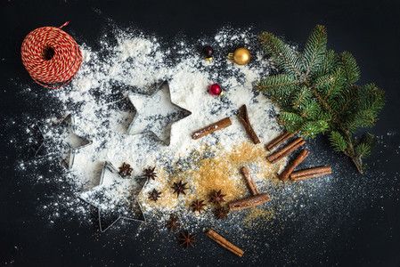 Cooking traditional Christmas holiday gingerbread cookies with cinnamon on black background