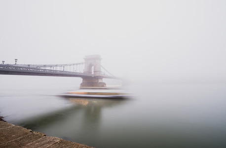 Chain Bridge over the Danube and a boat  Budapest  Hungary  in  fog  evening lights