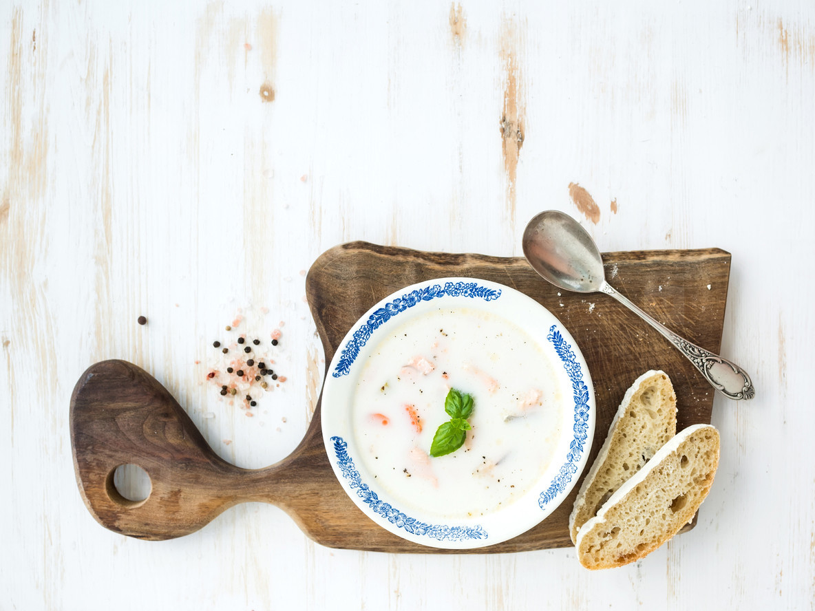 Scandinavian salmon soup with cream  fresh basil and bread in vintage ceramic plate on wooden serving board over white background  top view