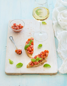 Tomato and basil bruschetta sandwich on white wooden serving board over rustic blue background  top view