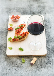 Wine appetizer set Glass of red wine brushettas with fresh tomato and basil on over rustic grunge grey surface