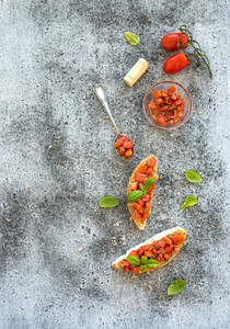 Tomato and basil bruschetta sandwich over grunge gray background  top view