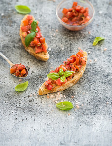 Tomato and basil bruschetta sandwich over grunge gray background top view