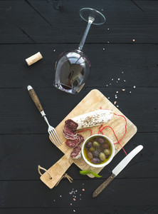 Wine appetizer set  Glass of red wine  French sausage and olives on black wooden backdrop  top view
