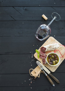 Wine appetizer set  Glass of red wine  French sausage and olives on black wooden backdrop