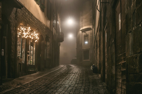Old European narrow empty street of medieval town on a foggy evening  Taken in Bergamo  Citta Alta  Lombardia