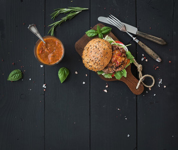 Fresh homemade burger on dark serving board over black wooden background  Top view