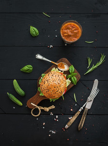 Fresh homemade burger on dark serving board with spicy tomato sauce sea salt and herbs over black wooden background Top view