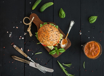Fresh homemade burger on dark serving board with spicy tomato sauce  sea salt