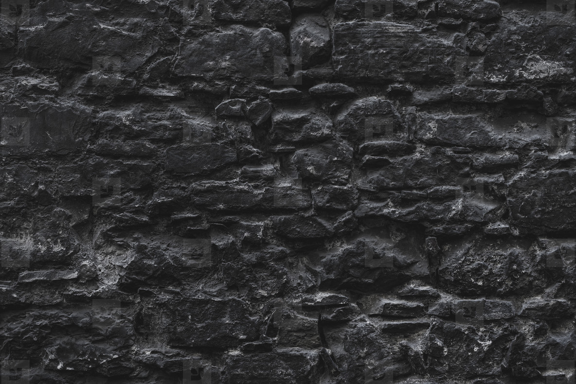 Dark brown old medieval natural stone wall  Texture  background or wallpaper