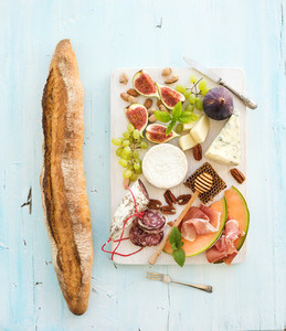 Wine and snack set  Baguette  figs  grapes  nuts  cheese variety  meat appetizers  herbs on light blue background  top view
