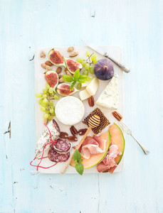 Wine snack set  Figs  grapes  nuts  cheese variety  meat appetizers and herbs on light blue background  top view