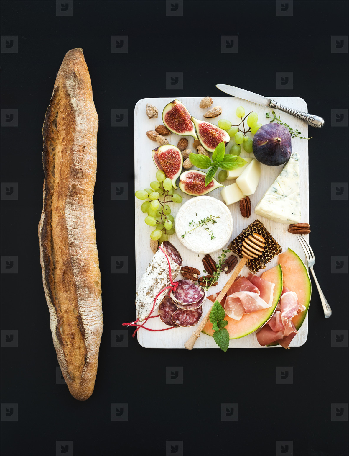 Wine and snack set  Baguette  figs  grapes  nuts  cheese variety  meat appetizers  herbs on white wooden board over black grunge background  top view