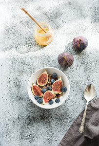Healthy breakfast Bowl of oat granola with yogurt fresh blueberries and figs over grunge grey backdrop