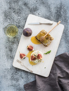 Camembert or brie cheese with fresh figs  honeycomb and glass of white wine on serving board over grunge rustic grey backdrop
