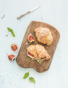 Freshly baked croissants with fresh figs and prosciutto on serving board over blue rustic wooden backdrop