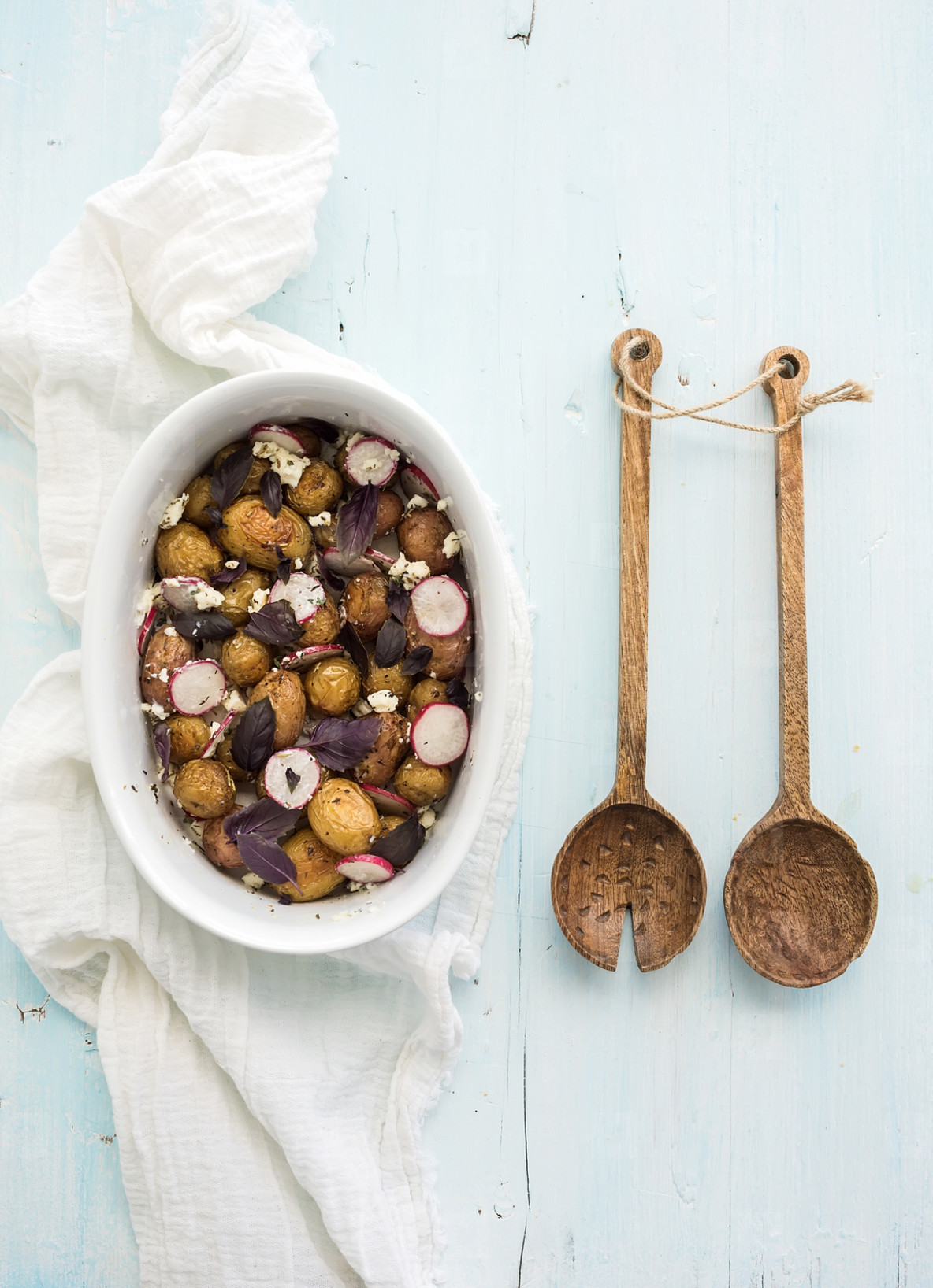 Roast young potato salad with radish and soft cheese in a baking dish over light blue background