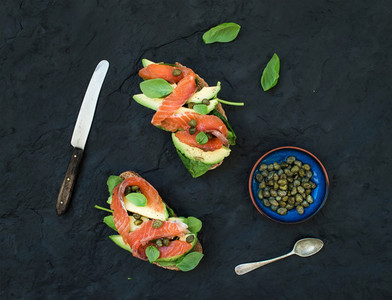 Sandwiches with smoked salmon  avocado  spinach  caper and basil over dark slate stone background