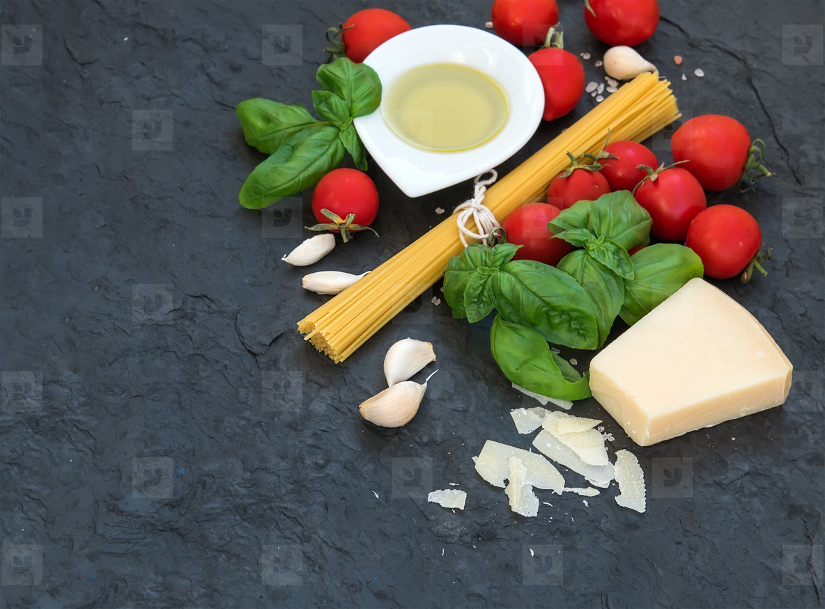 Ingredients for cooking pasta  Spaghetti  olive oil  garlic  Parmesan cheese  tomatoes and fresh basil on black slate background  top view  copy space