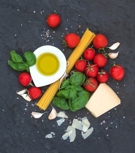 Ingredients for cooking pasta  Spaghetti  olive oil  garlic  Parmesan cheese  tomatoes and fresh basil on black slate background