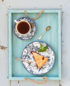 Piece of double crust plum pie and black tea in vintage porcelain cup  blue wooden tray  Top view