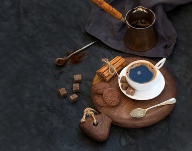 Cup of black coffee with chocolate biscuits  cinnamon sticks and cane sugar cubes on rustic wooden board over dark stone backdrop