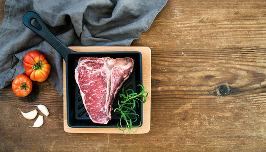 Raw uncooked meat t bone steak with garlic  heirloom tomatoes and rosemary in cooking pan over rustic wooden background