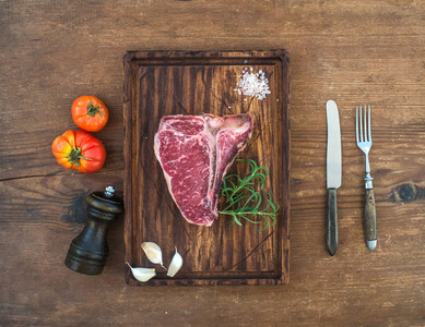 Raw fresh meat t bone steak with garlic cloves  tomatoes  rosemary  pepper and salt on serving board over rustic wooden background