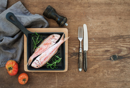 Raw uncooked Red Mullet fish in a cooking pan with rosemary  lemon and garlic over rustic wooden background