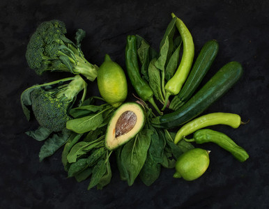 Raw green vegetables set Broccoli avocado pepper spinach zuccini and lime on  dark stone background