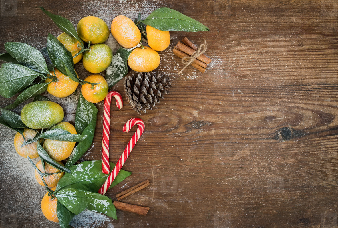 Christmas or New Year frame  Fresh mandarins with leaves  cinnamon sticks  pine cone and candy canes over rustic wooden background  top view
