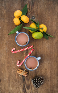Christmas or New Year attributes  Fresh mandarins with leaves  cinnamon sticks  pine cone  hot chocolate in mugs and candy canes over rustic wooden background  top view